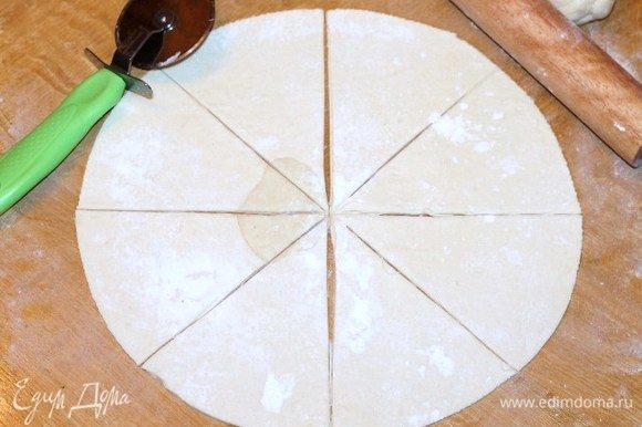 Приготовим тесто. Достаем размороженное тесто из упаковки. Присыпаем столешницу мукой и раскатываем тесто. Вырезаем круг диаметром 28 см. Разрезаем круг на 8 частей.
