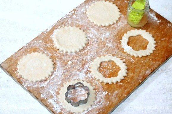 Приготовим волованы. На припыленную мукой разделочную доску кладем пластину теста. Не раскатывая тесто, вырезаем заготовки для волованов — это донышко и кольцо.