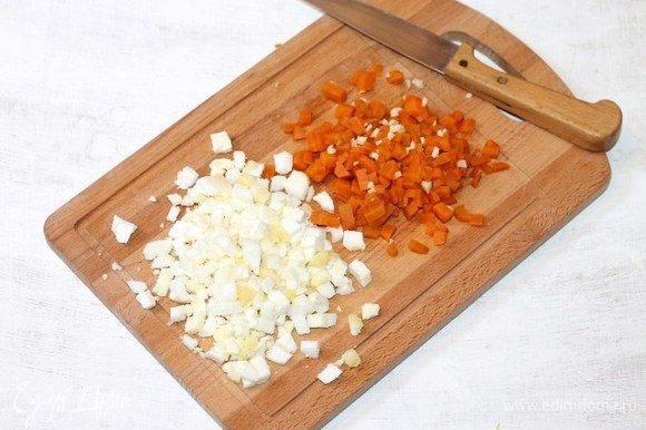 Очищенные и охлажденные морковь (небольшая) и вареные куриные яйца (2 шт.) нарезаем мелкими кубиками. Измельчаем очищенный зубчик чеснока и перемешиваем с морковью.