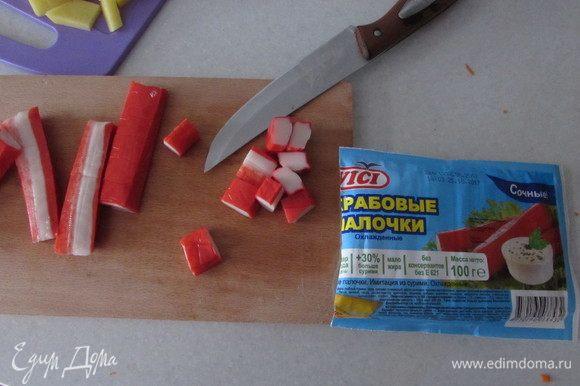 Нарезать крабовые палочки тоже крупными кубиками.