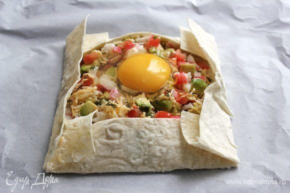 На этом этапе рекомендую корзинку из лаваша с начинкой перенести на противень, выложенный пергаментной бумагой и только после этого вбивать яйцо. Либо сразу начинять корзинку из лаваша на противне.