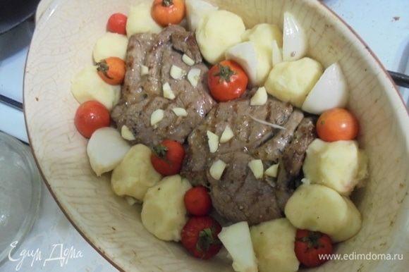 Лук очистить, нарезать на дольки, чеснок очистить и нарезать мелко. Огнеупорную форму для запекания смазать маслом, выложить кусочки баранины, вокруг — картофельные клецки, помидоры черри, кусочки лука и чеснока. Сбрызнуть оставшимся оливковым маслом, посыпать смесью перцев.