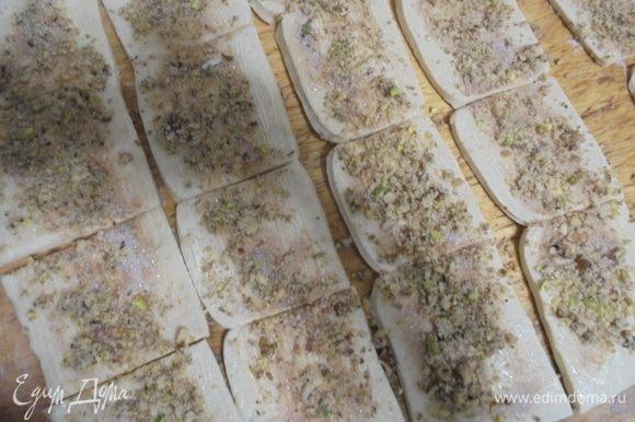 Посыпать полоски ореховой смесью и разрезать на квадратики размером примерно 5 на 5 см.
