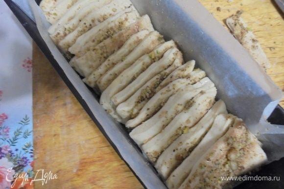 Прямоугольную форму для кекса выстлать бумагой для выпекания, смазать сливочным маслом и выложить полученные квадратики вертикально друг за другом. Оставить подходить в теплом месте 40-45 минут.