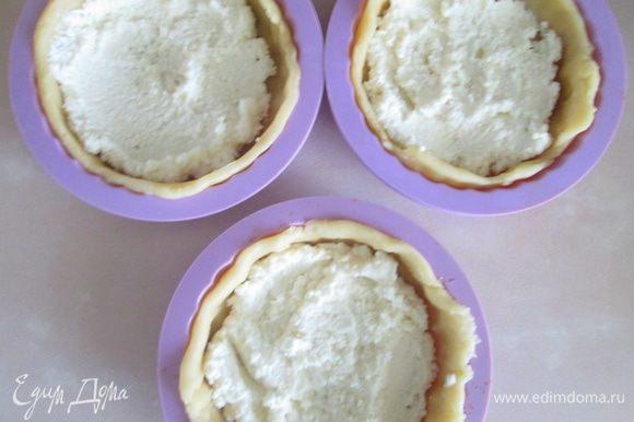 Первым слоем на тесто выложить творожную массу.