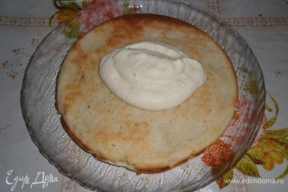 На тарелку выкладываем корж. Поверх коржа выкладываем 1-2 ст. л. приготовленного крема. Равномерно распределяем.