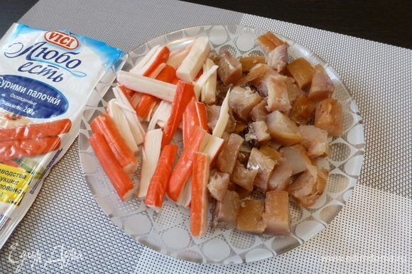 Белую рыбу и крабовые палочки нарежем кусочками.