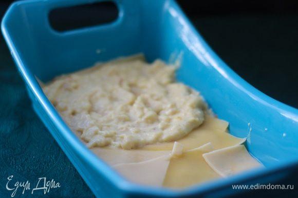 Смазать дно формы тонким слоем соуса, положить в один ряд листы лазаньи, сверху — четверть соуса, разровнять.