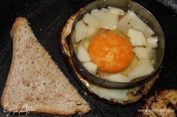 На белую часть яйца выложить кусочки сыра (в моем случае, это сыр азиаго, но подойдет российский, голландский), посолить. Я сразу же выложила кусочки хлеба, подсушить на сковороде. Закрыть крышкой, готовить 3 минуты на медленном огне. Не забудьте перевернуть хлеб.