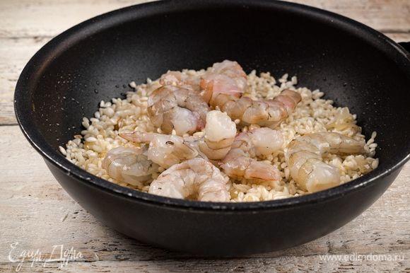 Креветки очистите и отправьте их жариться вместе с рисом.