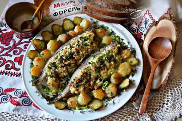 Готовую форель вместе с картофелем выложите на блюдо, украсьте солеными огурчиками и зеленью. Приятного аппетита и мир Вашему дому!