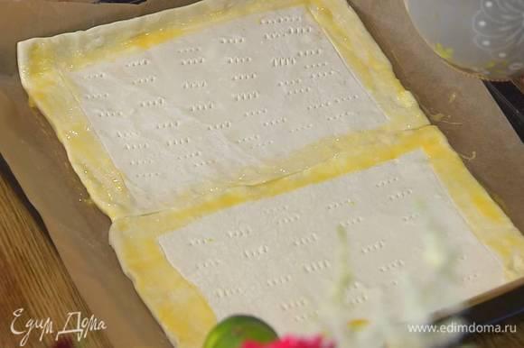 На противень, выстеленный бумагой для выпечки, поместить оба пласта теста, всю поверхность, кроме бортиков, часто наколоть вилкой, а бортики смазать яйцом.