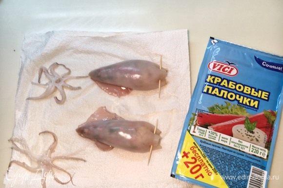 Набейте тушки кальмара смесью и плотно закрепите зубочистками.