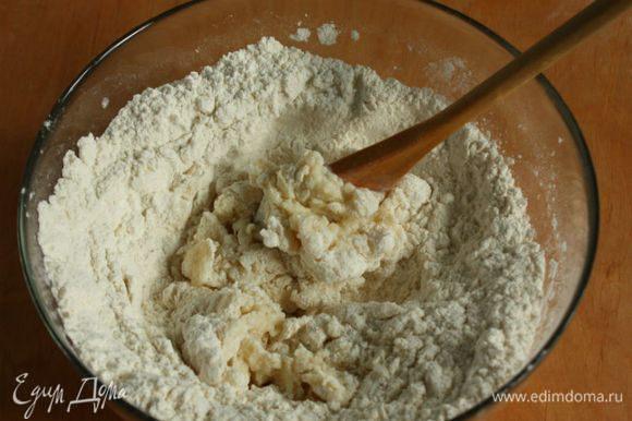 Вылить молочно-масляную смесь к муке и ложкой быстро перемешивать, подгребая муку с периферии. Когда тесто не будет обжигать, начинайте собирать его руками.