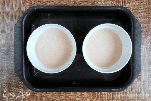 Распределить яичную смесь поровну по формам с карамелью. Пузырьки с поверхности крема можно убрать, аккуратно промокнув их бумажным полотенцем. Поместить формы в глубокий противень, а затем налить в него кипяток так, чтобы уровень воды доходил до середины форм. Накрыть противень фольгой и запекать 40-45 мин. (готовность проверить при помощи небольшого ножа, он должен выходить чистым, если проткнуть запеченный крем).