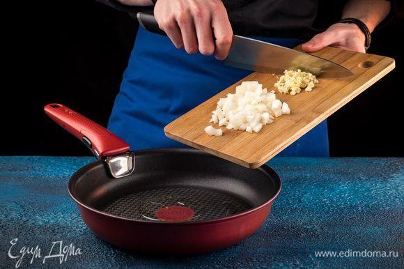 Лук измельчите, чеснок раздавите с помощью пресса. На сковороде разогрейте оливковое масло и поджарьте лук с чесноком до мягкости.