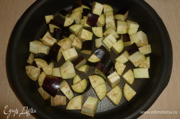 Разогреть духовку до 180°С. Баклажан и лук нарезать небольшими кусочками, сложить в форму для запекания.