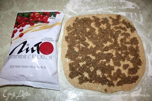 Приготовленную начинку из грецких орехов нужно разделить пополам и распределить по поверхности теста.