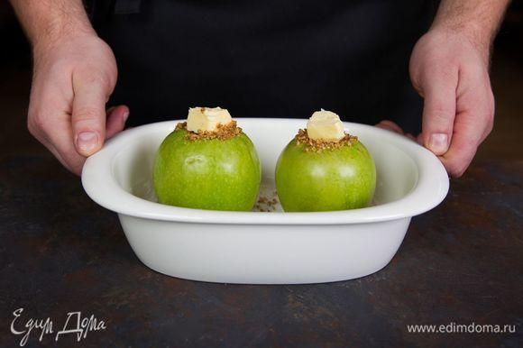 В каждое яблоко положите немного сахарно-ореховой смеси, а сверху — кусочек сливочного масла. Поместите яблоки в глубокую емкость для микроволновки.
