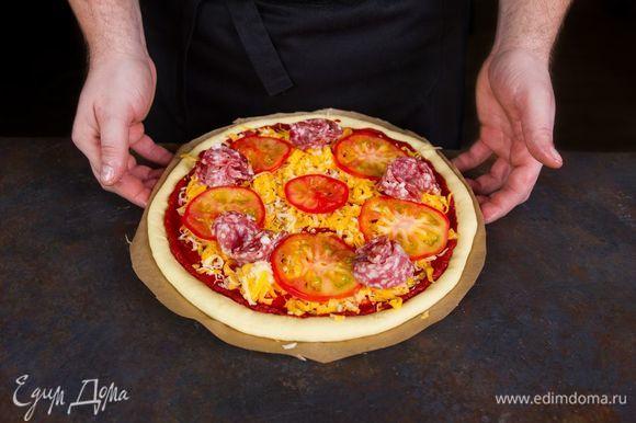 Выложите на тесто колбасу, помидоры, посыпьте сыром (используем половину).