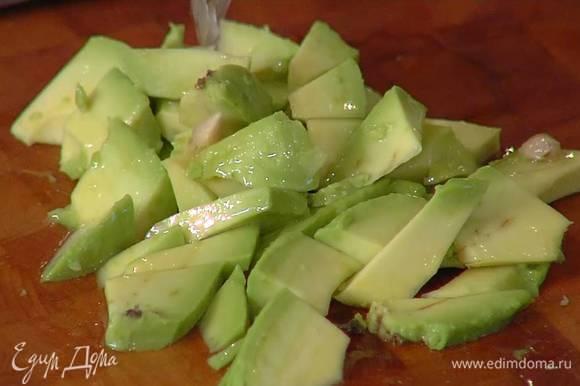 Авокадо почистить, нарезать небольшими кубиками и полить половиной лимонного сока.