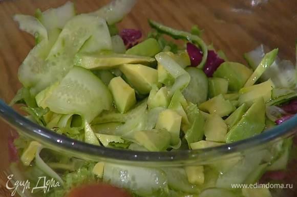 Листья салата выложить в глубокую посуду, добавить огурец, авокадо, полить оставшимся лимонным соком, оливковым маслом, посолить, поперчить и все перемешать, затем посыпать крупно порванными листьями кинзы.