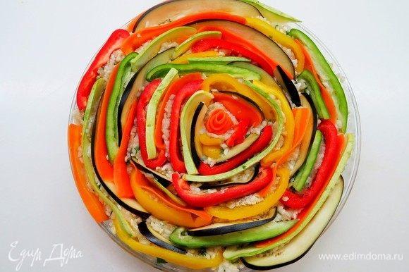 По окружности выложить овощи, вдавливая их в фарш по всей поверхности запеканки разноцветными кольцами.