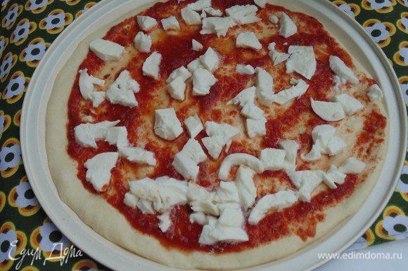 Моцареллу порезать небольшими кусочками. Смазать соусом пиццу, выложить моцареллу. Выпекать 10 минут.