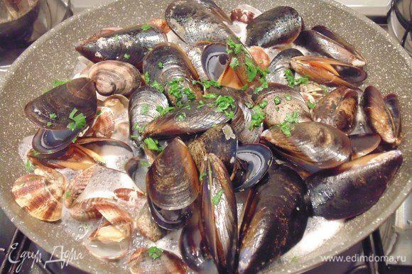 В сковороде разогреть 2 ст. ложки оливкового масла, добавить дольку чеснока, обжарить чеснок и затем его выкbнуть. Выложить морепродукты, влить вино, посыпать петрушкой, накрыть крышкой, дать раковинам открыться.