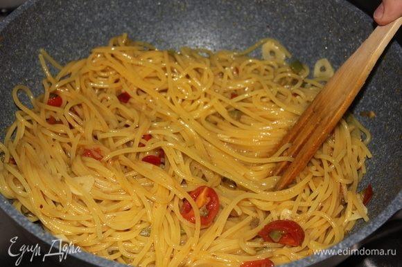 Примерно в течение 1,5 минут аккуратно, постоянно помешивая спагетти в сковороде, окончите готовить их. Если спагетти кажутся сухими, или выкипела вся жидкость, смело добавляйте немного воды, в которой варилась паста (спагетти).