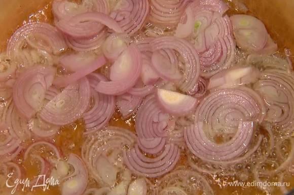 Разогреть в тяжелой кастрюле оливковое масло и обжарить лук, затем добавить сельдерей и еще немного обжарить.