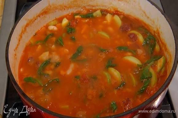 Когда бульон закипит, добавить помидоры в собственном соку, отваренную фасоль, нарезанный кабачок и готовить минут семь, затем посолить, отправить в суп измельченный руками пеперончино, шпинат, охотничьи колбаски и еще немного подержать на огне.