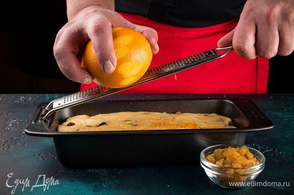 Смажьте форму растительным маслом, выложите в нее тесто, накройте его пищевой пленкой и поставьте в теплое место на 1,5 часа. С апельсина мелкой теркой снимите цедру. В готовое тесто добавьте цедру и сухой изюм. Перемешайте, чтобы все распределилось равномерно.