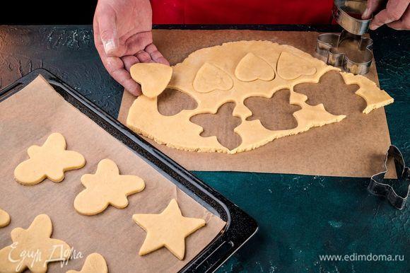 С помощью разных формочек вырежьте из теста фигурки: звездочки, человечков, снеговиков, елки. Противень застелите пергаментом, выложите на него заготовки печенья. Выпекайте в духовке 15 минут при 180°С.