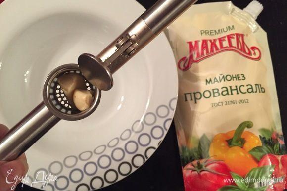 Берем миску, чеснокодавилку, чеснок и майонез ТМ «МахеевЪ». Выдавливаем чеснок.