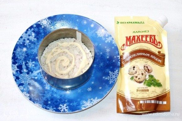 Берем сервировочное блюдо и ставим на середину формовочное кольцо. Дно смазываем майонезом ТМ «МахеевЪ» и выкладываем куриное филе, смазываем майонезом.