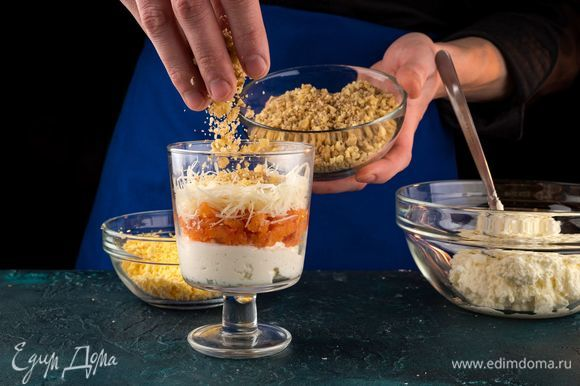 Выкладывайте ингредиенты салата в бокал слоями: творожный сыр с белками и хреном, рыба, твердый сыр, орехи, творожный сыр с хреном.