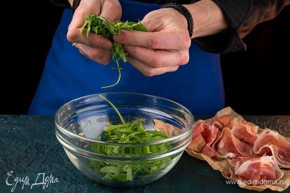 Нарежьте прошутто очень тонкими широкими ломтиками. Пучок руколы порвите руками.