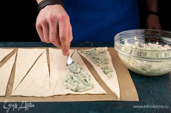 Каждый треугольник смажьте сырной начинкой, отступив место от краев по 2 см.