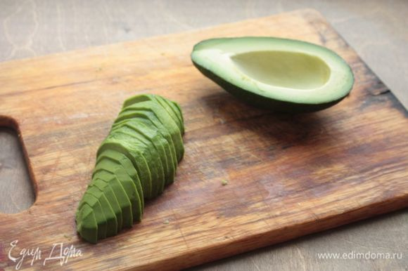 Из авокадо удалите косточку, а также очистите от шкурки. Нарежьте дольками толщиной 3–4 мм.