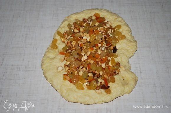 Растянем тесто и посыпем изюмом, цукатами и порезанным миндалем, я добавила немного грецких орехов.
