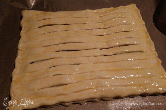 Накрыть начинку раскрытым пластом теста с разрезами. Смазать верх пирога яичным желтком. Выпекать в духовке при 200°С, 20-25 минут до золотистого цвета.