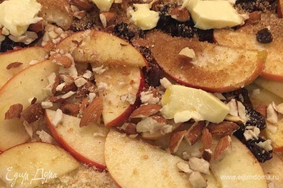 Тесто, смазанное сливочным маслом, посыпаем сухарями, выкладываем яблоки, сахар с корицей, изюм и орехи, кусочки сливочного масла. Оставляя при этом с одного края свободное место см 10 на захлест.