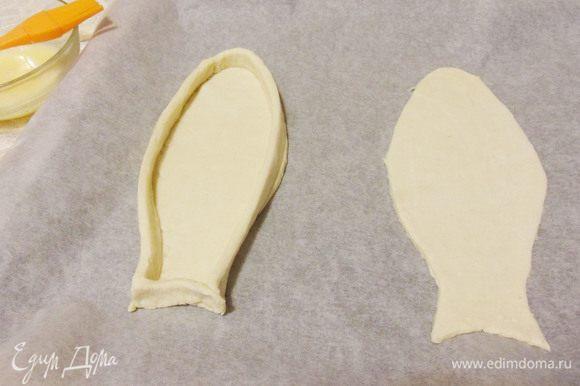 Переложить заготовки на противень застеленный бумагой для выпечки. Из обрезков теста вырезать длинные полоски, смазать их с одной стороны яйцом. Выложить полоски «бортиками» по краю рыбки, смазанной стороной вниз.