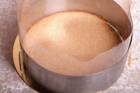 Приступить к сборке торта. Для этого стенки кольца простелить ацетатной пленкой. На дно выложить первый песочный корж. Корж может слегка раскрошиться — не переживайте, в готовом торте это будет незаметно.