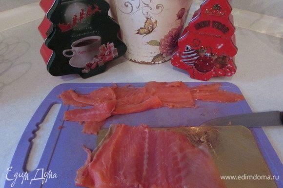 Нарезать ломтиками слабосоленого лосося.