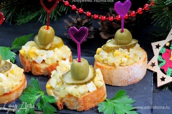 Огурец нарезать кружочками и выложить на бутерброды поверх салата. На кольцо огурчика кладем зеленую оливку и прокалываем бутерброд шпажкой. Вкусных вам праздников!