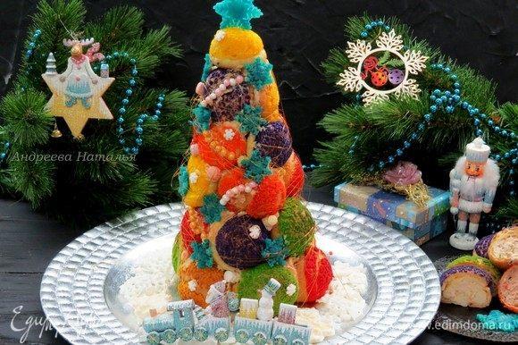Затем аккуратно извлекаем затвердевший конус из бумажной оболочки. Ставим на блюдо и украшаем по своему желанию. Я сделала классические карамельные нити, украсила сахарными бусинами и снежинками из марципана.