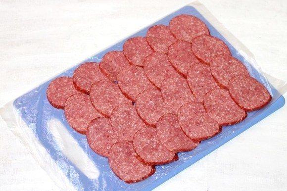 Застилаем пленку на разделочную доску и выкладываем кружочки колбасы.