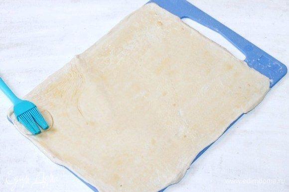 Напыляем мукой разделочную доску и раскатываем слоеное тесто до увеличения в два раза.